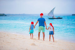 Happy family in Santa Hats on summer vacation. Christmas holidays with young family of four enjoying their sea trip Royalty Free Stock Photo