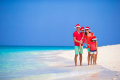 Happy family in Santa Hats during tropical Christmas vacation. Happy family of four in Christmas Hats during tropical vacation Stock Images