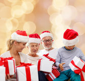 Happy family in santa helper hats with gift boxes Stock Images
