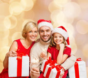 Happy family in santa helper hats with gift boxes. Christmas, holidays,  family and people concept - happy mother, father and little girl in santa helper hats Stock Photos