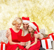 Happy family in santa helper hats with gift boxes Stock Photography