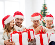 Happy family in santa helper hats with gift boxes Royalty Free Stock Images