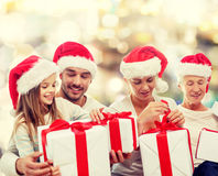 Happy family in santa helper hats with gift boxes Stock Photos