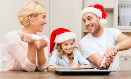 Happy family in santa helper hats making cookies Royalty Free Stock Photos