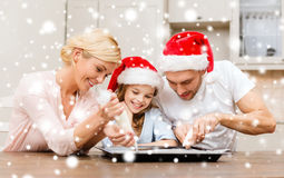 Happy family in santa helper hats making cookies Royalty Free Stock Image