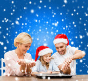 Happy family in santa helper hats making cookies Stock Photography