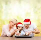 Happy family in santa helper hats making cookies Stock Photo