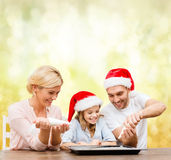 Happy family in santa helper hats making cookies Stock Photos