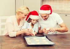 Happy family in santa helper hats making cookies Stock Images