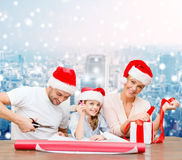 Happy family in santa helper hats packing gift Stock Photos