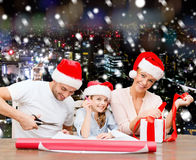 Happy family in santa helper hats packing gift Royalty Free Stock Image