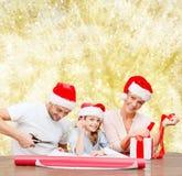 Happy family in santa helper hats packing gift Stock Photo