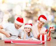 Happy family in santa helper hats packing gift Stock Images