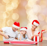 Happy family in santa helper hats packing gift Royalty Free Stock Photography