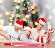 Happy family in santa helper hats packing gift Royalty Free Stock Images
