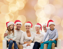 Happy family in santa helper hats sitting on couch Royalty Free Stock Images
