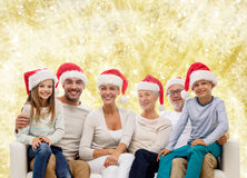 Happy family in santa helper hats sitting on couch Royalty Free Stock Photography