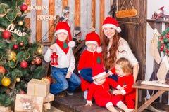 Happy family in Santa`s costumes near Xmas tree Royalty Free Stock Photography