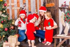 Happy family in Santa`s costumes near Xmas tree Stock Photo