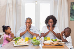 Happy family saying grace before meal. At home in the kitchen Royalty Free Stock Photography