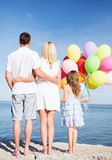 Happy family at the seaside with bunch of balloons Royalty Free Stock Images