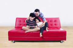 Happy family seated on a couch in living room Royalty Free Stock Photos