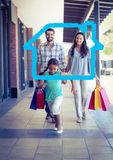 Happy family with shopping bag laid with house shape walking in corridor. Digital composition of happy family with shopping bag laid with house shape walking in Stock Photo