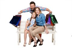 Happy family with shopping bags sitting at studio Stock Images