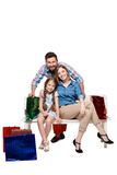Happy family with shopping bags sitting at studio Royalty Free Stock Image