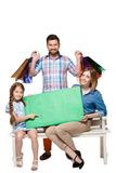 Happy family with shopping bags sitting at studio Royalty Free Stock Photos