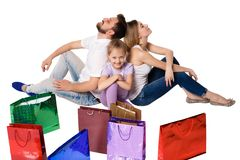 Happy family with shopping bags sitting at studio Stock Photo