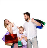 Happy family with shopping bags standing at studio Royalty Free Stock Photography
