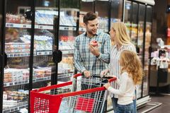 Happy family with shopping cart in supermarket. Store stock photo