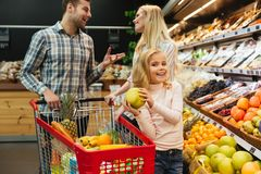 Happy family with shopping cart. In supermarket store Stock Images