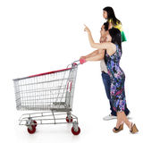 Happy family with shopping cart. Three member of happy family pushing shopping cart and looking at copyspace stock images