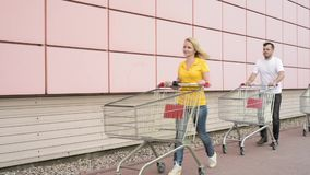 Happy family with shopping carts. In a parking lot near a supermarket. People walk and are engaged in purchases in shopping centre. Mom, Dad and Children having stock footage