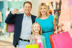 Happy family shopping. Cheerful family holding shopping bags and smiling at camera while standing in shopping mall royalty free stock photo