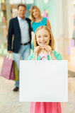 Happy family shopping. Cheerful family shopping in shopping mall while little girl showing her shopping bags and smiling stock photography