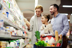 Happy Family Shopping in Supermarket. Portrait of happy family shopping in grocery store: choosing milk in dairy product department with cart full of food stock photos