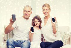 Happy family showing smartphones blank screens Royalty Free Stock Photography