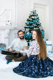 Happy family sing Christmas Carols under a fir-tree. They sit on a white fluffy carpet royalty free stock images