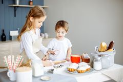 Happy family sister and brother baking cookies in the kitchen royalty free stock image