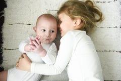 Sister girl hugs newborn brother royalty free stock photos