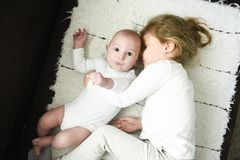 Sister girl hugs newborn brother stock photos