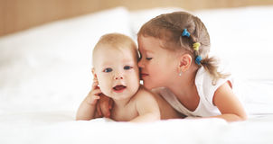 Happy family sister kisses baby brother Stock Images