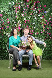 Happy family sit on bench with bunch of flowers Stock Image