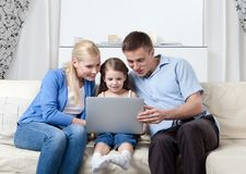 Happy family sit on the couch with laptop Stock Images