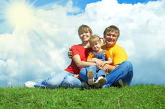 Happy family sit on green grass under sky. With clouds Stock Photo