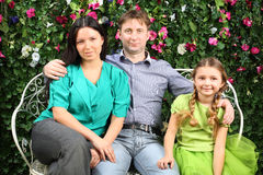 Happy family sit on white bench in garden Stock Photo