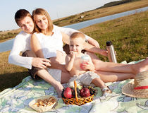 Happy family siting on field Royalty Free Stock Photo